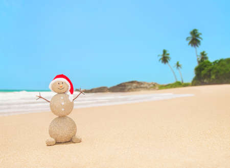 Christmas sandy snowman in red santa hat at palm ocean beach. Holiday concept for New Years Cards. Stock Photo