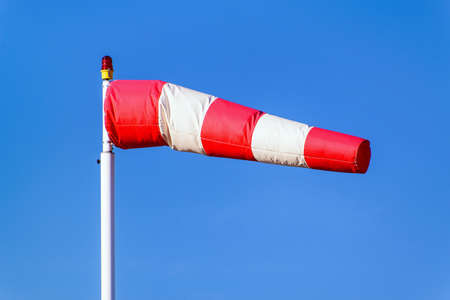 indicate: Airport windsock on clear blue sky background in windy weather indicate the local wind direction (also called: air sock, drogue, wind sleeve, wind cone) Stock Photo