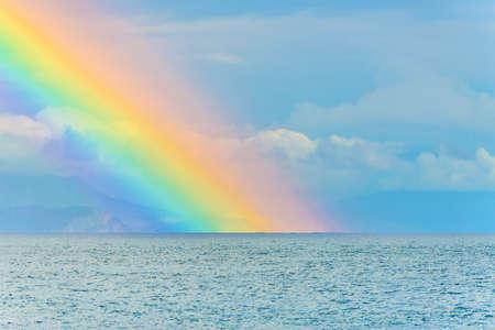 Hermoso paisaje marino con gran arco iris brillante en las nubes después de la lluvia por encima de la superficie de las olas del mar y las montañas