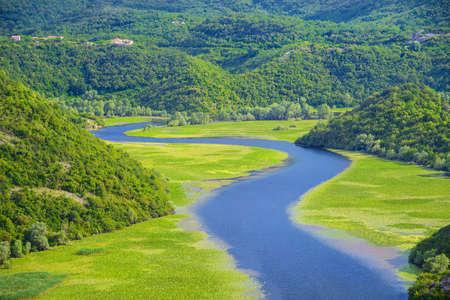 Skadar 호수 국립 공원, 몬테네그로, 자연 풍경 배경에서 녹색 산 뒤에 구불 구불 한 리예 카 Crnojevica 강.
