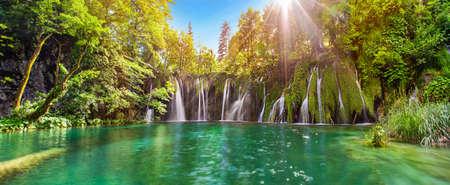 Verbazend Panorama van de waterval in Plitvice Lakes National Park, Kroatië, Europa. Majestueus uitzicht met turquoise water en zonnig zonsondergang balken, reisbestemmingen achtergrond