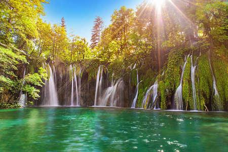 プリトヴィツェ湖群国立公園, クロアチア、ヨーロッパの素晴らしい滝。壮大なターコイズ ブルーの海と夕日の日当たりの良い梁旅行目的地背景