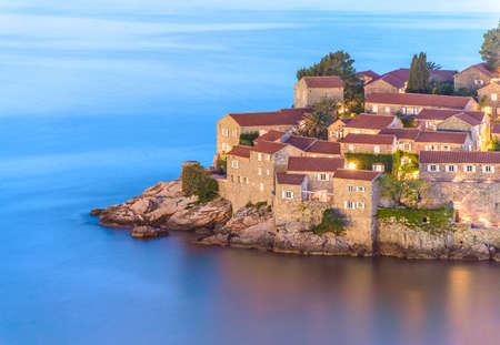 Night closeup view to Sveti Stefan with lighting in windows, small islet and hotel resort in Montenegro, southeast of Budva. Balkans, Adriatic sea, Europe. Travel destinations background.