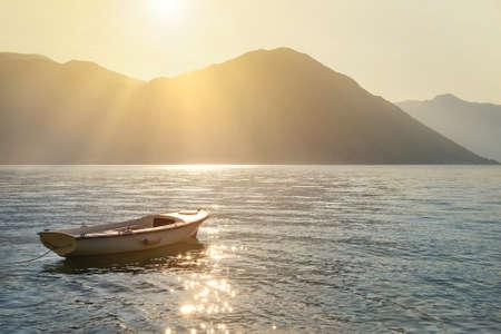 boka: Fishing boat on moorage at sunlight glittering sea surface against sunset Lovcen mountain background with sun rays. Montenegro, Kotor Bay (Boka Kotorska).