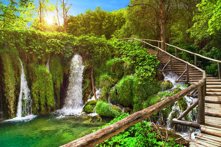 Amazing waterfall in Plitvice Lakes National Park, Croatia, Europe. Majestic view with turquoise water, wooden handrail stairs, and sunset sunny beams, travel destinations background Stock Photo