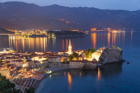 walled: Budva old medieval walled city lights at night. Center of Montenegrin tourism, medieval walled city at Adriatic sea coastline. Montenegro. Europe.