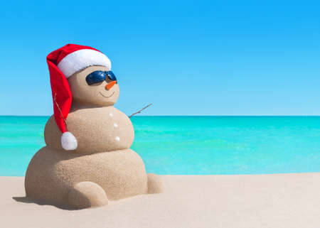Happy sandy snowman in Christmas Santa Claus hat and sunglasses at sunny sea beach, New Year holiday vacation concept for traveling to hot south countries