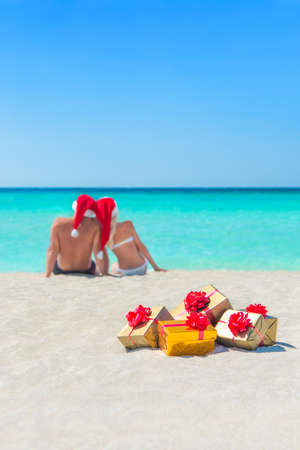 family vacation: Many gift boxes at beach sand against the sea water, sky, and sunbathing man and woman romantic couple in red Santa hats, Christmas and New Year holidays travel concept