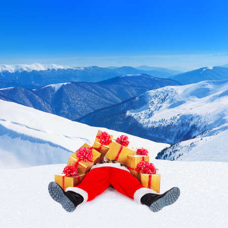 Funny Santa Claus spread out legs heap up with many Christmas golden gift boxes wrapped with red bows for children lying on snow against winter mountain landscape and blue sky,New Year holiday concept