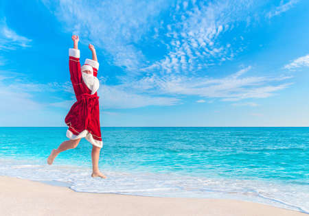kringle: Santa Claus (Father Christmas) jump at sea sandy beach in the sky - New Years vacation in hot countries concept