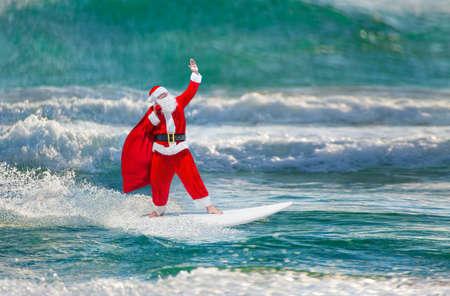 Kerstman windsurfer met grote vakantie geschenken zak te gaan surfen met surfplank bij oceaangolven spatten in winderig weer - Nieuwjaar en Kerstmis actieve sport lifestyle concept