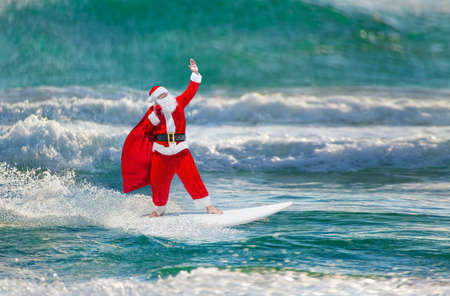 Santa Claus windsurfer with large holiday gifts sack go surfing with surfboard at ocean waves splashes in windy weather - New Year and Christmas active sports lifestyle concept