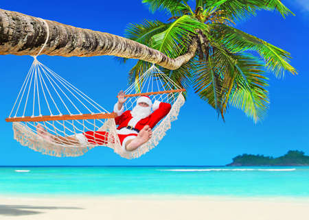 Santa Claus relaxing at sun in white cozy mesh hammock under coconut palm tree shadow at tropical paradise sandy ocean beach - New Year and Christmas travel holidays concept