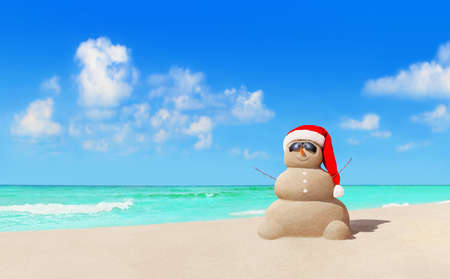 Positive sandy Snowman in red Christmas Santa Claus hat and sunglasses at sunny tropical beach. New Year concept for travel destinations in hot tourist countries