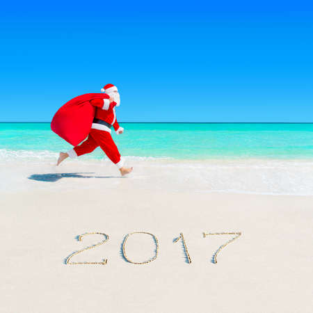 Christmas Santa Claus running on the jump at tropical ocean white sandy beach with large red sack full of gifts and surprises, season 2017 New Year vacation and travel agencies price discounts concept Stock Photo