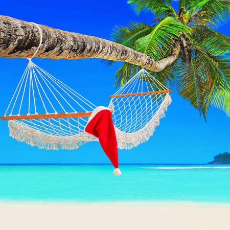 Santa Claus hat on wooden mesh hammock on perfect tropical white sandy coconut palm beach Baie Lazare, Mahe island, Seychelles, Indian Ocean