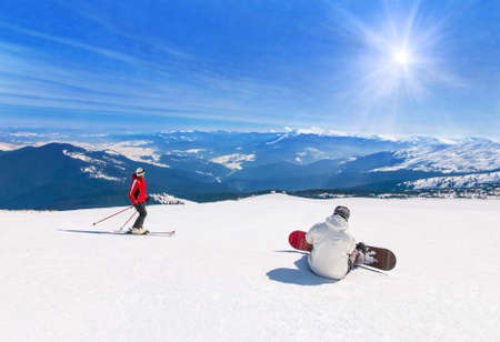 Skier and snowboarder skiing and snowboarding downhill in high snowy mountains against sun sunshine, active winter sports holidays travel at ski health resort concept Standard-Bild