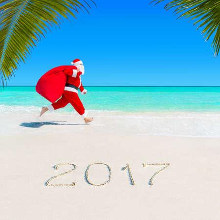 크리스마스 산타 클로스 바다에서 실행 열 대 모래 팜 비치 선물 - 시즌 2017 새 해 휴가 및 여행사 가격 할인 개념의 전체와 함께 큰 자루 스톡 콘텐츠