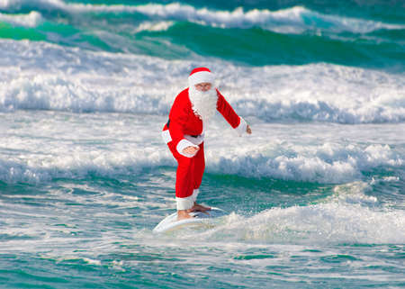 sailboard: Santa Claus windsurfer go surfing with surfboard at ocean waves splashes in windy weather - New Year and Christmas active sports lifestyle concept Stock Photo