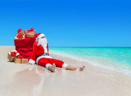 Christmas Santa Claus with sack full of golden gift boxes with red bows resting at ocean tropical sandy beach - travel destinations for vacation to hot countries concept