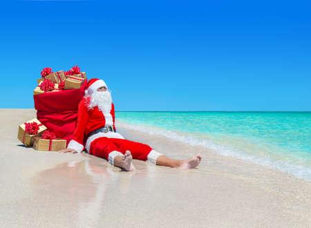Kerstmis de Kerstman met een zak vol gouden geschenkdozen met rode bogen rust op de oceaan tropisch zandstrand - reisbestemmingen voor vakantie naar warme landen begrip Stockfoto