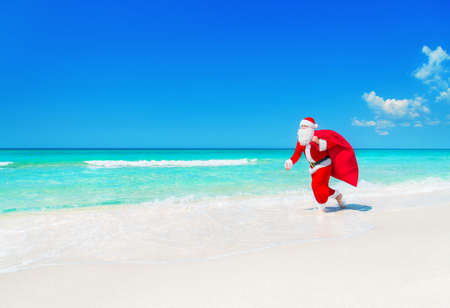kringle: Christmas Santa Claus running with big gifts sack hurry on present it for children along tropical sandy ocean beach - New Year travel agencies price reductions concept