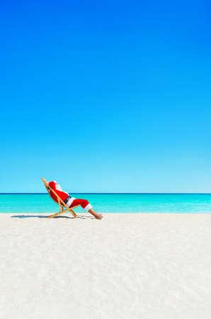 산타 클로스 sunlounger 바다에서 편안한 열 대 모래 해변 - 크리스마스와 새 해 여행 휴가 목적지 개념