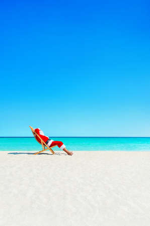 Santa Claus relaxing in sunlounger at ocean tropical sandy beach - Christmas and New Year travel vacation destinations concept Stock Photo