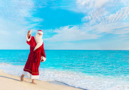rest: Santa Claus (Father Christmas) walking at beach - New Years vacation in hot countries concept