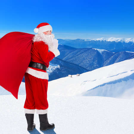 furtively: Santa Claus with big Christmas bag full of gifts against village in snowy winter mountains forest and blue sky landscape, coming for wish children a happy New Year holiday