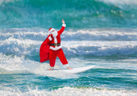 sailboard: Santa Claus windsurfer with large holiday gifts sack go surfing with surfboard at ocean waves splashes in windy weather - New Year and Christmas active sports lifestyle concept