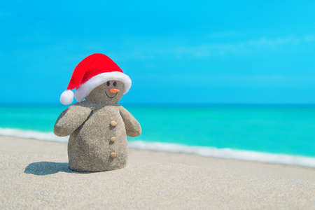 beach happy new year: Funny sandy Snowman in red Santa hat and orange carrot at sunny beach. Happy New Year and Christmas holidays concept for travel in tropical countries and resorts