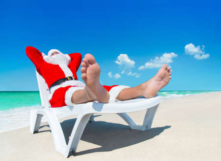 Christmas Santa Claus sunbathe on sunlounger at tropical ocean beach, heels at foreground - New Year travel vacation in hot countries concept Stock Photo