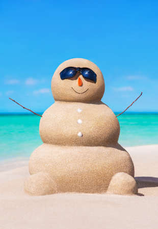 vacationer: Funny sandy snowman in black sunglasses and carrot nose at tropical ocean beach. Holiday concept for New Year and Christmas travel destinations to hot coastal countries. Stock Photo
