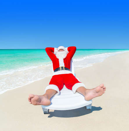 vacationer: Christmas Santa Claus relax on sunlounger at tropical ocean sandy beach, heels at foreground - New Year travel vacation in hot countries concept