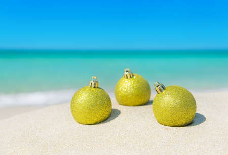 Three golden christmas tree balls decorations shining at sun on tropical ocean beach sand  - winter New Year holidays in hot countries concept