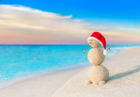 destinations: Christmas positive Sandy Snowman in red Santa Claus hat at ocean sunset beach. New Year vacation discounts in hot countries destinations concept