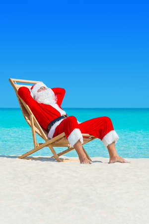 Christmas Santa Claus lounge in wooden deckchair at ocean tropical sandy beach - New Year travel destinations vacation in hot countries concept, vertical seascape Stock Photo