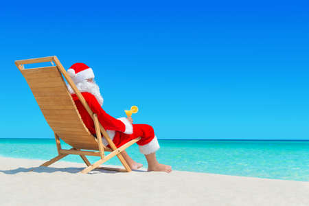 Christmas Santa Claus relax on wooden sunlounger with fresh orange juice cocktail at ocean tropical sandy beach - New Year travel destinations in hot countries concept 스톡 콘텐츠