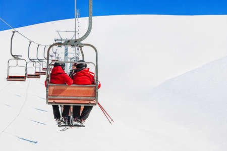 Skiers couple in red skisuits go on a ski lift against snowy mountains landscape and blue sky - winter holidays concept