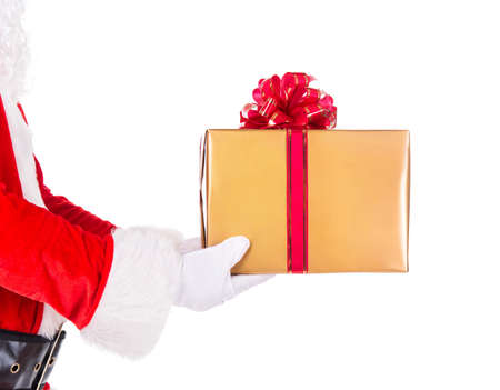 Santa Claus hand in red fur costume and white gloves holding golden wrapped Christmas gift box with big bow isolated on white background