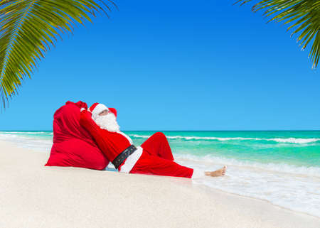Santa Claus sunbathing on big Christmas sack full of gifts at ocean beach under palm leaves shadow - xmas or New Year travel destinations concept