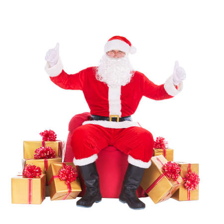 Santa Claus sitting at big red Christmas sack and golden presents, gifts and surprises around isolated on white background, thumbs up gesturing. Happy New Year or Merry Xmas holiday concept