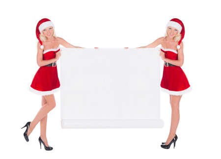 Two happy cute blonde cheerful Santa women with christmas white paper scroll advertising poster isolated on white background