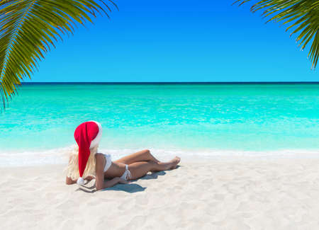 Cute blonde Snow Maiden woman in Santa hat take pleasure sunbathing at tropical ocean palm beach, Christmas and New Year travel destinations to vacation in hot countries concept