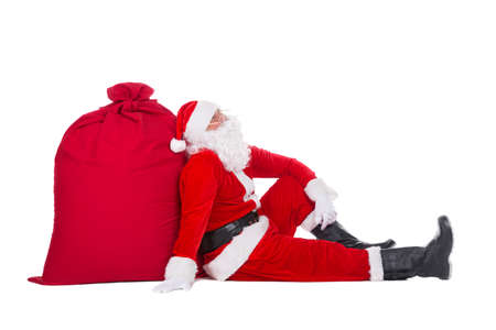 Santa Claus have rest sitting near big Christmas sack full of presents, gifts and surprises isolated on white background, New Year or xmas holiday concept