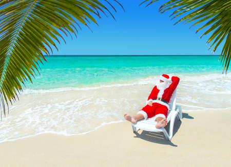 クリスマス サンタ クロースが海洋熱帯の砂浜のパームビーチでサンラウンジャーでリラックス - 暑い南の国のコンセプトにクリスマスと新年の旅行 写真素材