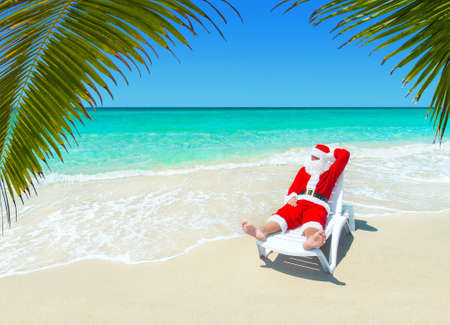 sunbath: Christmas Santa Claus relax in sunlounger at ocean tropical sandy palm beach - Xmas and New Years travel destinations to hot south countries concept Stock Photo