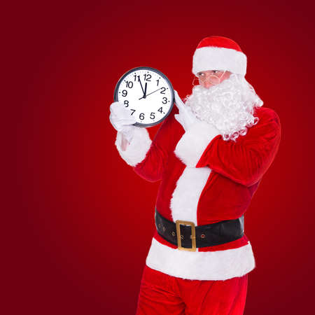 Christmas Santa Claus pointing at clock showing five minutes to midnight on red background. Happy New Year concept.