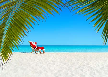 クリスマス サンタ クロース サンラウンジャー海砂浜ヤシの下で熱帯のビーチでのリラックスを残します。暑い国の概念に幸せな新年の旅行の目的 写真素材